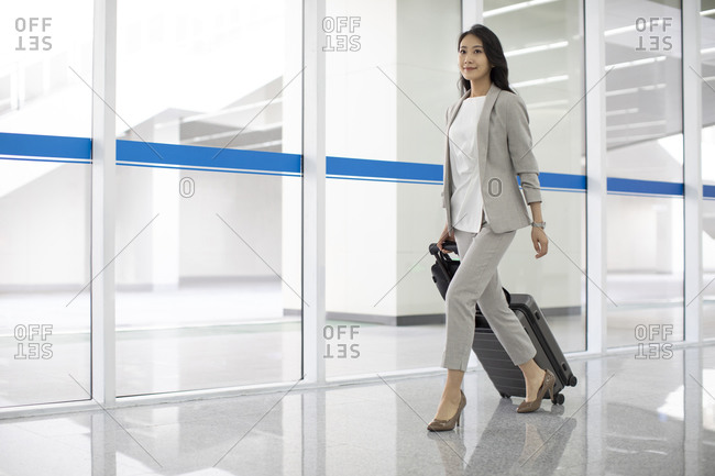 Young Chinese businesswoman walking with luggage in airport