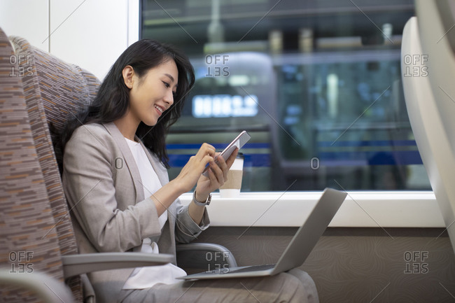Young Chinese businesswoman using smartphone on high-speed train