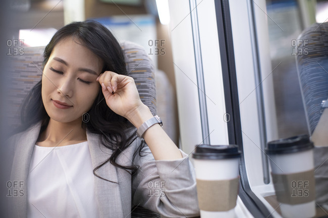 Young Chinese businesswoman resting on high-speed train