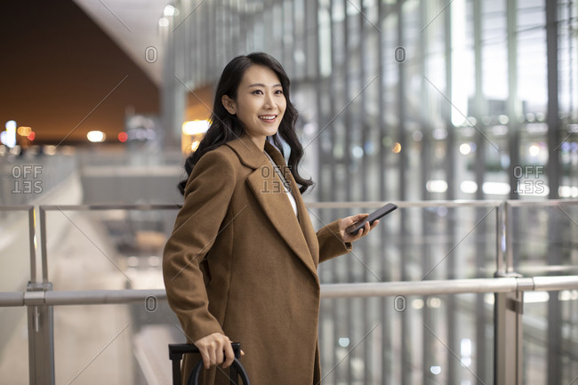 Young Chinese businesswoman using smartphone in airport
