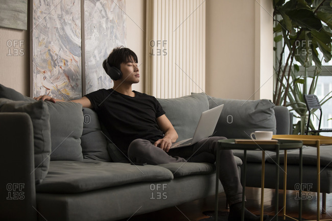 Young Chinese man relaxing at home