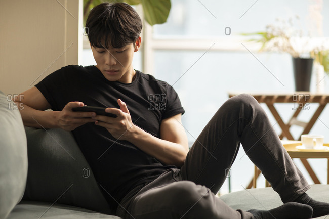 Young Chinese man playing mobile games at home