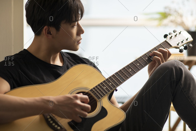 Young Chinese man playing guitar at home