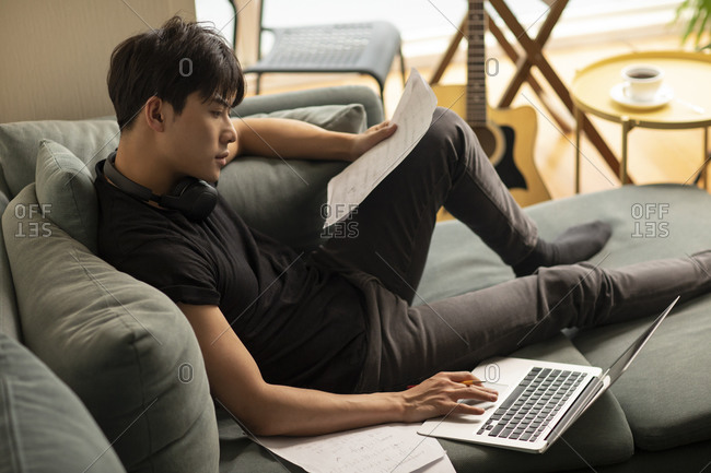 Young Chinese man composing music at home