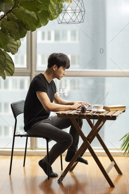 Young Chinese photographer using laptop at home