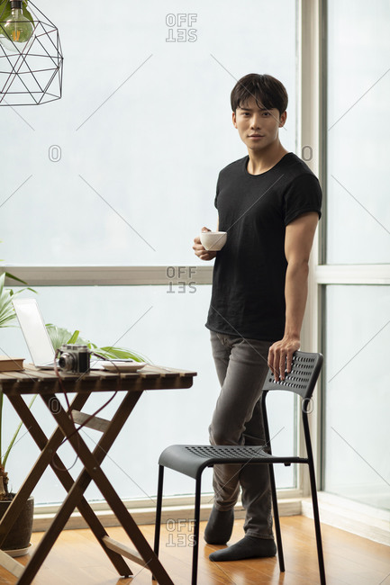 Young Chinese photographer drinking coffee at home