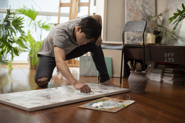 Young Chinese man painting at home