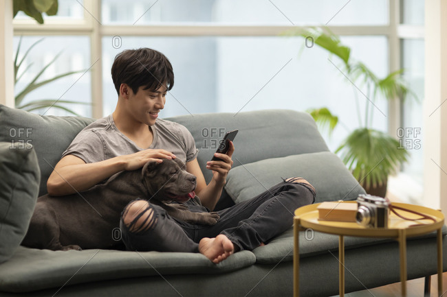 Young Chinese man with pet dog on sofa