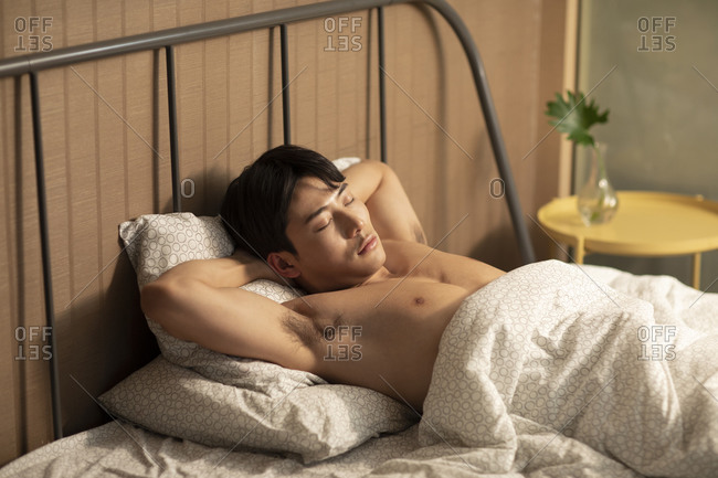 Young Chinese man sleeping in bed