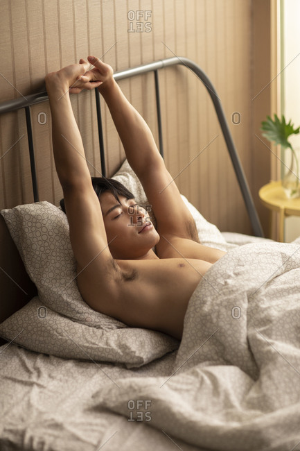 Young Chinese man waking up in the morning