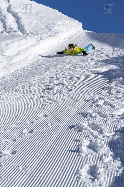 Europe, Switzerland, valais, belalp, boy slides down a snowy winter hiking trail