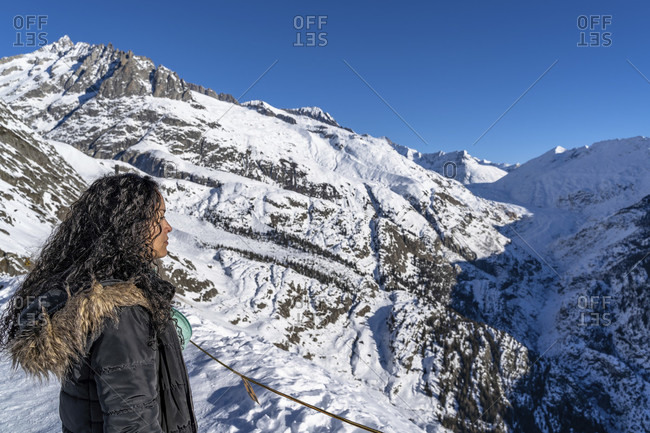 Europe, Switzerland, valais, belalp, young woman looks at the wintry aletsch glacier