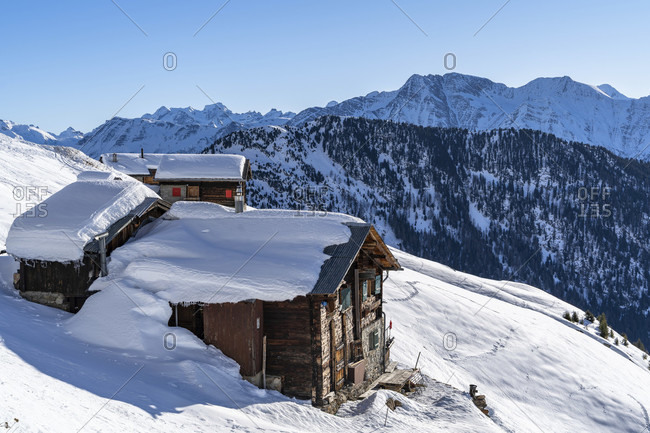 Europe, Switzerland, valais, belalp, snow-covered wooden huts against the backdrop of the lepontine alps