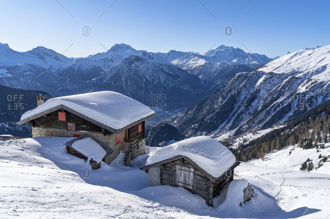 Europe, Switzerland, valais, belalp, snowed-in wooden huts against the mountain backdrop of the valais alps