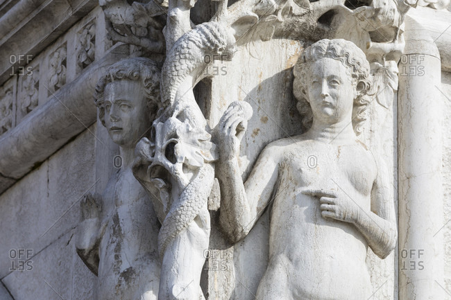 March 23, 2018: adam and eve corner figure at doge's palace, st. mark's square, venice, veneto, italy