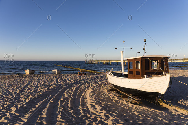 Fishing boats on the beach in front of the pier, koserow seaside resort, usedom island, mecklenburg-west pomerania, Germany