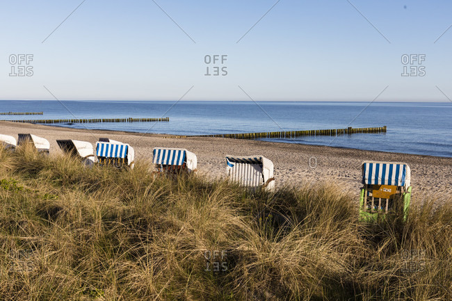 View over dune grass to beach chairs and groynes in the calm baltic sea, ostseebad kuhlungsborn, mecklenburg-west pomerania, Germany