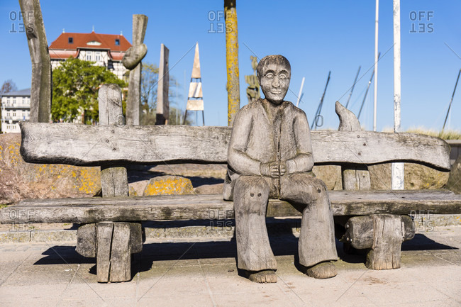 May 6, 2018: wooden figure and bench in front of sculpture garden on the promenade, ostseebad kuhlungsborn, mecklenburg-west pomerania, Germany
