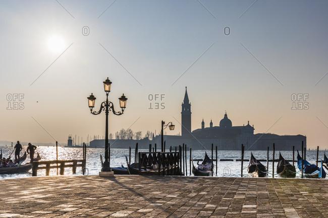 January 21, 2018: gondolas on st. mark's square with a view of san giorgio maggiore island, back light, venice, veneto, italy