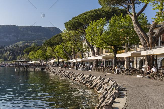 April 19, 2018: promenade on the harbor with a view to rocca di garda, garda, lake garda, verona province, veneto, italy