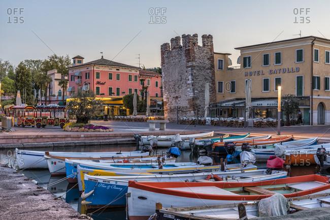 April 20, 2018: hotel catullo (3 *) and historic town tower at the harbor, bardolino, lake garda, verona province, veneto, italy