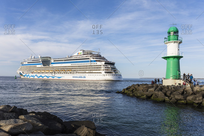 May 4, 2018: expiring cruise ship aida diva with lighthouse at the port entrance, anemone seaside resort, rostock, mecklenburg-west pomerania, Germany