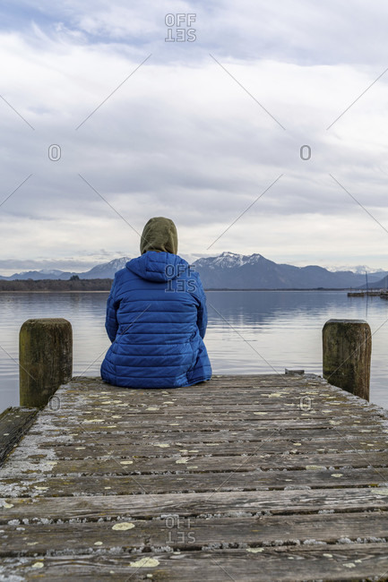 Europe, Germany, bavaria, rosenheim, prien am chiemsee, chiemsee, man sits on jetty and looks across the chiemsee to the chiemgau alps