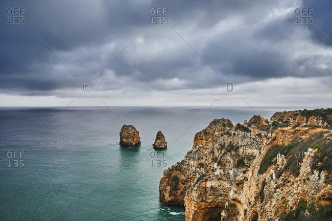 Europe, portugal, algarve, litoral, barlavento, felsalgarve, faro district, lagos, coastline of the ponta da piedade, with offshore rock reef, overcast with clouds