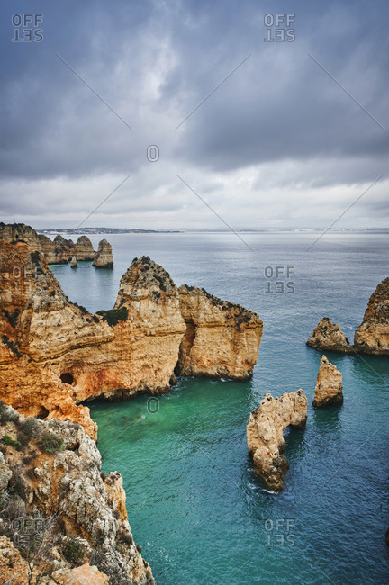 Europe, portugal, algarve, litoral, barlavento, felsalgarve, district faro, lagos, ponta da piedade, lagoon with reef and distant view, cloud formations, portrait format