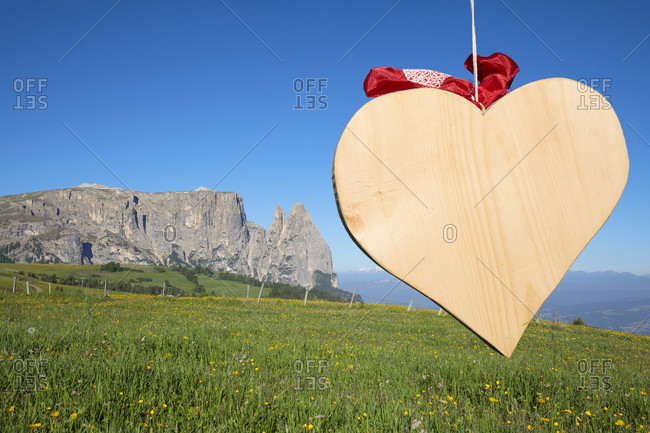 The shape of a wooden heart, in the background the scilir, alpe di siusi (seiser alm), castelrotto (kastelruth), dolomites, south tyrol, italy