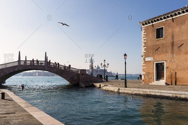 January 21, 2018: bridge on the canal to campo arsenale in front of the church of san giorgio maggiore, venice, veneto, italy