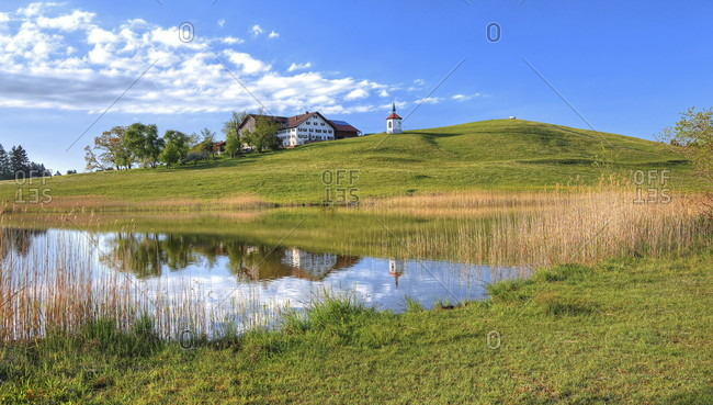 Spring landscape at hegratsrieder weiher with a small chapel at the hamlet of hegratsried, halblech, romantische strasse, ostealgia, algae, swabia, bavaria, Germany