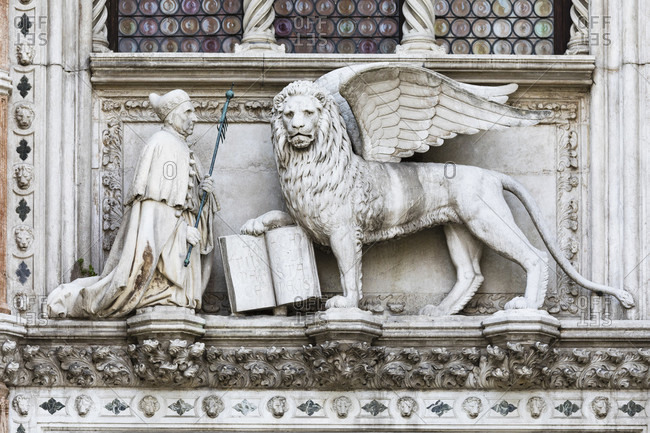 March 23, 2018: figure group with kneeling doge francesco foscari in front of the st. mark lion on the entrance portal porta della carta, venice, veneto, italy