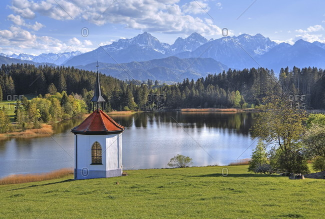 Spring landscape at the hegratsrieder weiher near the hamlet of hegratsried with a small chapel against the tannheim mountains, halblech, romantic road, ostealgia, algae, swabia, bavaria, Germany