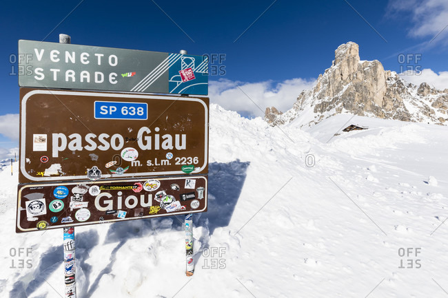 February 24, 2018: sign of the pass summit at passo di giau with ra gusela (2595m) in the background, winter, cortina d'ampezzo, dolomites, province of belluno, veneto, italy