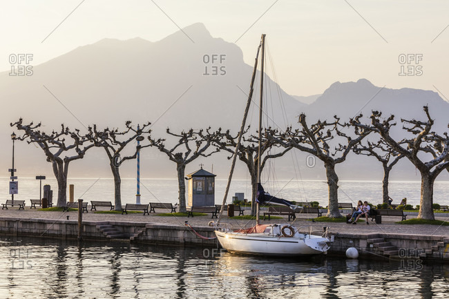 April 18, 2018: sailboat in the harbor in front of the mighty mountains on the west side of the lake, sunset, torri del benaco, lake garda, verona province, veneto, italy