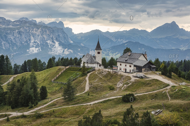 April 25, 2020: heilig kreuz hospiz refuge and pilgrimage church at the foot of the heiligkreuzkofel, in background puez-geisler nature park, hochabtei / alta badia, bolzano province, south tyrol, italy, europe