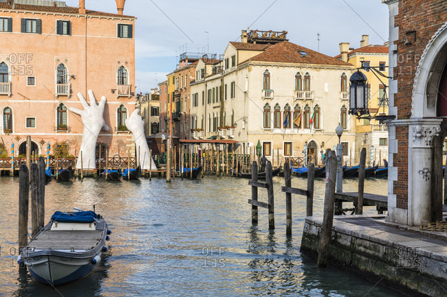 "February 25, 2018: campo de la pescaria, view from the fish market to the ca 'sagredo and the sculpture ""support"", huge children's hands support the palazzo, reference to climate change, by artist lorenzo quinn, grand canal, venice, venezia, venice province, veneto, italy"