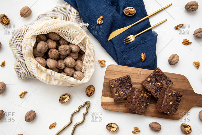 Top view of stacked brownies and nuts on white background