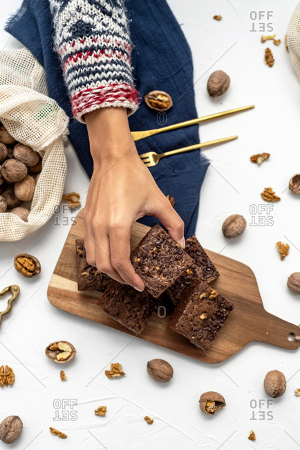 Top view of a hand taking stacked brownies on white background with nuts