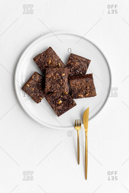 Top view of fresh brownie pieces on white plate with golden cutlery