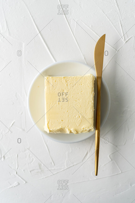 Top view of butter on white plate and golden knife on white background