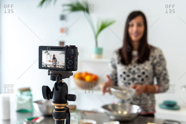 Woman recording video of her cooking gingerbread men for online video blog on Christmas