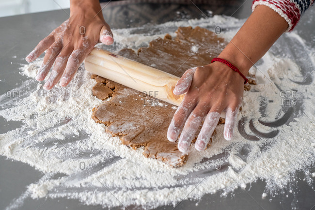 Woman rolling out gingerbread dough with a rolling pin