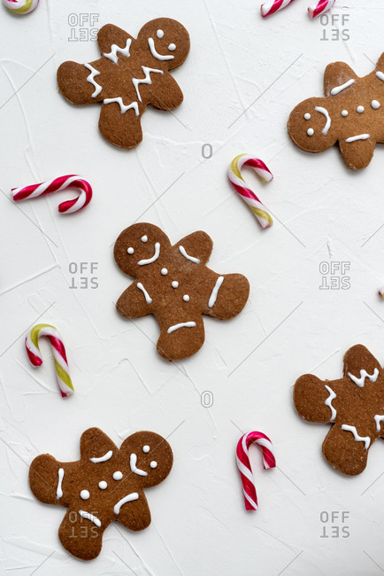 Christmas candy cans and gingerbread man cookies on white background