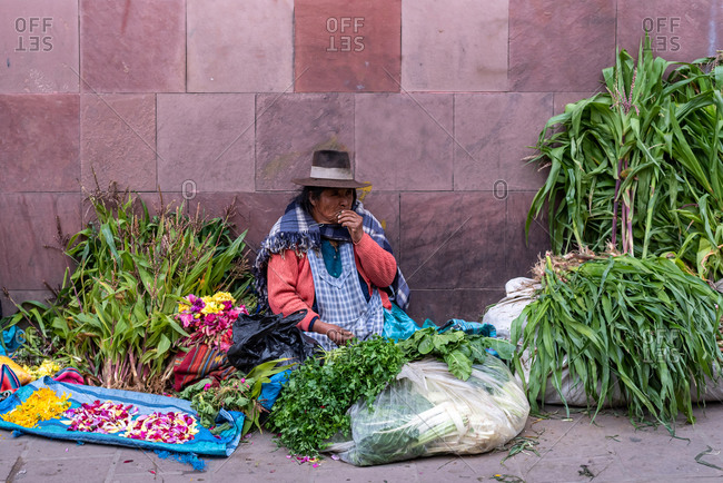 February 24, 2020: Woman wearing traditional clothes and selling vegetables on the street. Potosi, Bolivia