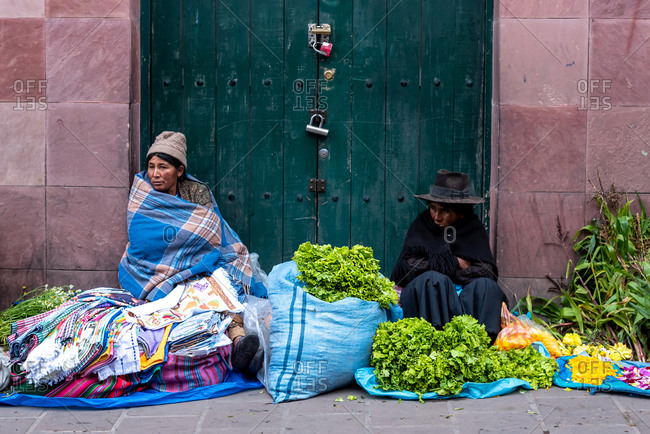 February 24, 2020: Women wearing traditional clothes and selling fabrics, flowers and vegetables on the street. Potosi, Bolivia