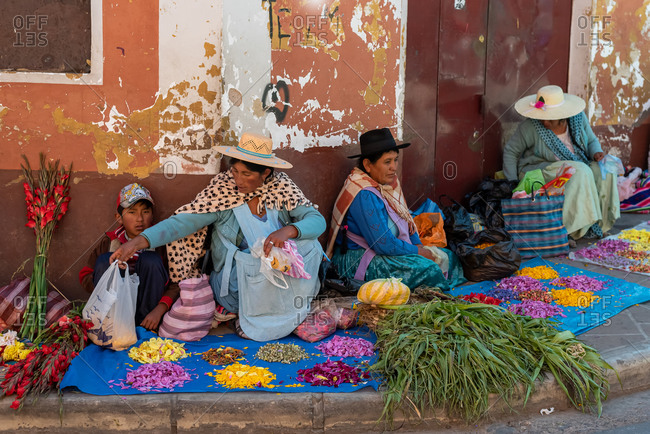 February 25, 2020: Women wearing traditional clothes and selling fabrics, flowers and vegetables on the street. Potosi, Bolivia