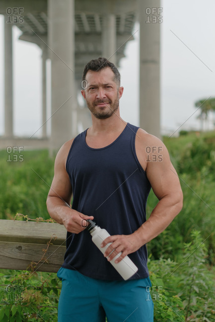 Fit man taking a water break after working out