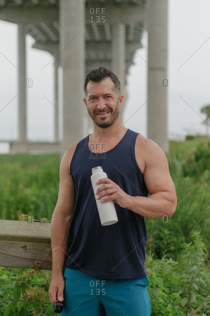 Middle-aged athletic man taking a water break after working out